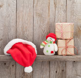 Christmas gift boxes, santa hat and snowman toy Royalty Free Stock Photo
