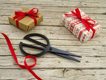 Christmas gift boxes, scissor and ribbon on wooden backgroun. Christmas gift boxes, scissor and red ribbon on wooden background Stock Photos