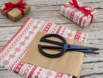 Christmas gift boxes, scissor and ribbon on wooden backgroun. Christmas gift boxes, scissor and red ribbon on wooden background Royalty Free Stock Photo
