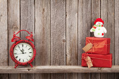 Christmas gift boxes, snowman and alarm clock Royalty Free Stock Photos