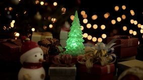 Christmas gift boxes, snowman and Christmas tree with blinking lights on glow bokeh light background.  stock footage