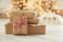 Christmas gift boxes. Some paper parcels (christmas gift boxes) wrapped with paper kraft and tied with red & white baker's twine in a white wooden table Stock Photo