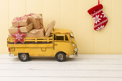 Christmas gift boxes. Some paper parcels (christmas gift boxes) wrapped with paper kraft and tied with red & white baker's twine in a yellow truck Stock Photo