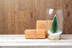 Christmas gift boxes and tree in glass jar over wooden background Royalty Free Stock Photo