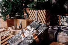 Christmas gift boxes under the fir tree. Craft, silver, white and black colors of ribbons and paper Stock Images