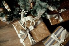 Christmas gift boxes under the fir tree. Deer toy on a box. Christmas gift boxes under the fir tree. craft, silver, white and black colors of ribbons and paper Stock Photography