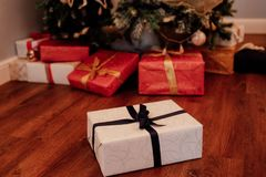 Christmas gift boxes under the fir tree. Red and white paper with the black, red and gold ribbons Royalty Free Stock Images