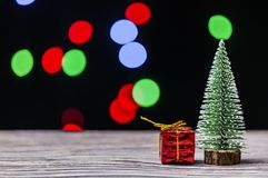 Christmas gift boxes under pine tree on wooden table over bokeh background stock image