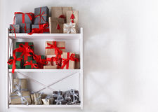 Christmas gift boxes on white shelves at wall background Stock Photos