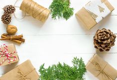 Christmas gift boxes wrapped in brown craft paper tied with twine pine cones juniper cinnamon nuts arranged in circle on wood stock photo