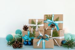 Christmas gift boxes wrapped of craft paper, blue and white ribbons and Christmas lights on the blue and white background. Stock Images