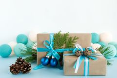 Christmas gift boxes wrapped of craft paper, blue and white ribbons, decorated of fir branches, pine cones and Christmas balls. Stock Photos