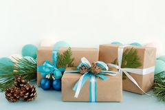 Christmas gift boxes wrapped of craft paper, blue and white ribbons, decorated of fir branches, pine cones and Christmas balls. Stock Photo