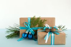 Christmas gift boxes wrapped of craft paper, blue and white ribbons, decorated of fir branches, pine cones and Christmas balls. Royalty Free Stock Images