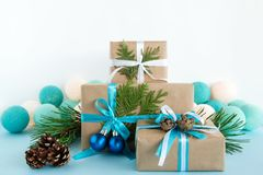 Christmas gift boxes wrapped of craft paper, blue and white ribbons and Christmas lights on the blue and white background. Three Christmas gift boxes wrapped of Royalty Free Stock Photos