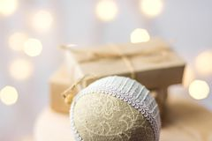 Christmas gift boxes wrapped in craft paper tied with twine linen fabric ornament ball on wooden chair. Golden garland bokeh light. S. Holiday preparation royalty free stock photos