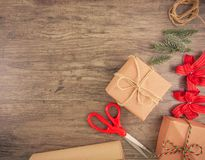 Christmas gift boxes with wrapping tools. Christmas gift box and wrapping tools flat lay on wooden background with copy space royalty free stock images