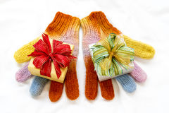 Christmas gift boxs with rainbow winter gloves on white backgro Royalty Free Stock Photo