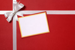 Christmas gift card and envelope, white ribbon bow, red wrapping Royalty Free Stock Image