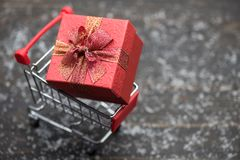 Christmas gift in cart over snow wood. Christmas holiday gift shopping concept on wooden background with winter snow and copy space for text. xmas present box on stock images
