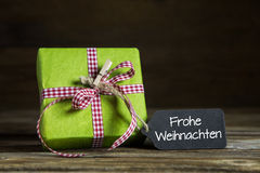 Christmas gift certificate with german text on wooden background. With a present. Text: Merry Christmas royalty free stock photography