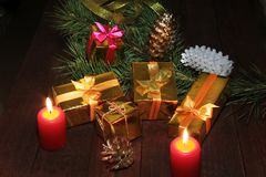 Christmas gift colored boxes, cones, Christmas tree and candles on a wooden table. Composition of celebrities. Selective. Focus Stock Photo