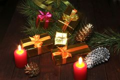 Christmas gift colored boxes, cones, Christmas tree and candles on a wooden table. Composition of celebrities. Selective. Focus Royalty Free Stock Images