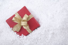 Christmas gift covered with snow Stock Images