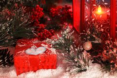 Christmas gift covered with snow in the light of a red lantern on the background of New Year`s scenery. Christmas and New Year card Stock Photo
