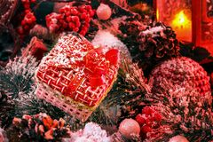 Christmas gift covered with snow in the light of a red lantern on the background of New Year`s scenery. Christmas and New Year Royalty Free Stock Image