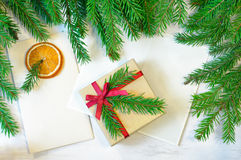 Christmas gift decorated with Christmas tree twig, envelope and Royalty Free Stock Images