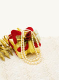 Christmas gift decoration and pearls. Celebrating Christmas with golden festive decorations and vintage pearls stock photography