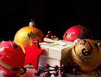 Christmas gift and decorations. With red star and Christmas-tree balls against dark background Stock Photo
