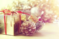 Christmas gift and decorations against defocussed backgrouond. Gold Christmas gift and decorations against a defocussed lights background Stock Image