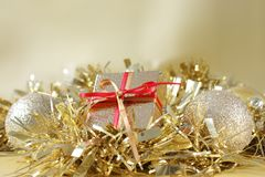 Christmas gift and decorations in gold tinsel. Christmas gift with red ribbon and decorations in gold tinsel Stock Images