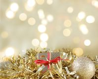 Christmas gift and decorations nestled in gold garland. Against bokeh lights background Stock Photo