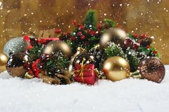 Christmas gift and decorations nestled in snow. With snow falling Royalty Free Stock Images