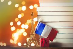 Christmas gift with Eiffel tower toy and pile of books. With fairy lights on background Royalty Free Stock Images