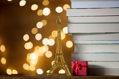 Christmas gift with Eiffel tower toy and pile of books. With fairy lights on background Royalty Free Stock Photos