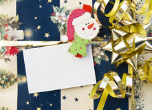 Christmas gift with empty card. Detail of a decorated christmas gift and a snowman holding an empty card Royalty Free Stock Image