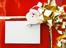 Christmas gift with empty card. Detail of a decorated christmas gift and santa holding an empty card Royalty Free Stock Image