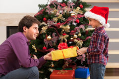 Christmas gift from father. Christmas gift for a boy from his father royalty free stock images