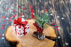 Christmas gift and fir branch with cone is situated on a tree st. Ump. On dark background Stock Photos