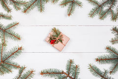 Christmas gift and fir branches in form of frame on white wooden table. Xmas and Happy New Year composition.Flat lay Stock Images