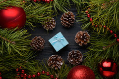 Christmas gift with fir branches, pine cones on old wooden board Royalty Free Stock Images