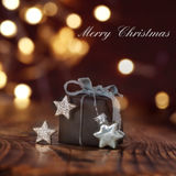 Christmas gift in front of festive background Stock Image