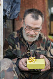 Christmas gift. Frustrated homeless man with his little christmas gift Stock Photo