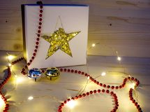 CHRISTMAS GIFT - GIFT BOX WITH GOLDEN STAR AND LIGHT CHAIN. Gift box with golden star and CHRISTMAS LIGHT CHAIN Stock Photo