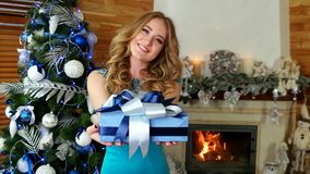 Christmas gift, girl gives a festive wrapped present, portrait of female with Christmas gift in hand, on Christmas Eve stock video