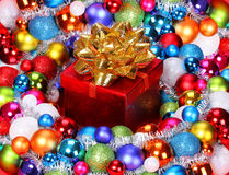 Christmas Gift with Gold Bow and Colorful Balls. Royalty Free Stock Photography